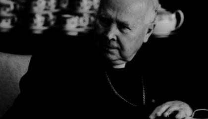 Postać arcybiskupa Tadeusza Gocłowskiego, siedzącego przy stole podczas rady nadzorczej fundacji.