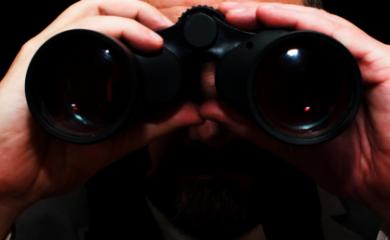 Mężczyzna patrzący przez lornetkę - jako symbol pracodawcy, poszukującego kandydata do pracy.