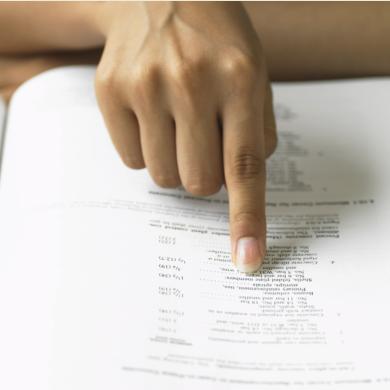 Na grafice widać dłoń wskazującą konkretny zapis w książce.