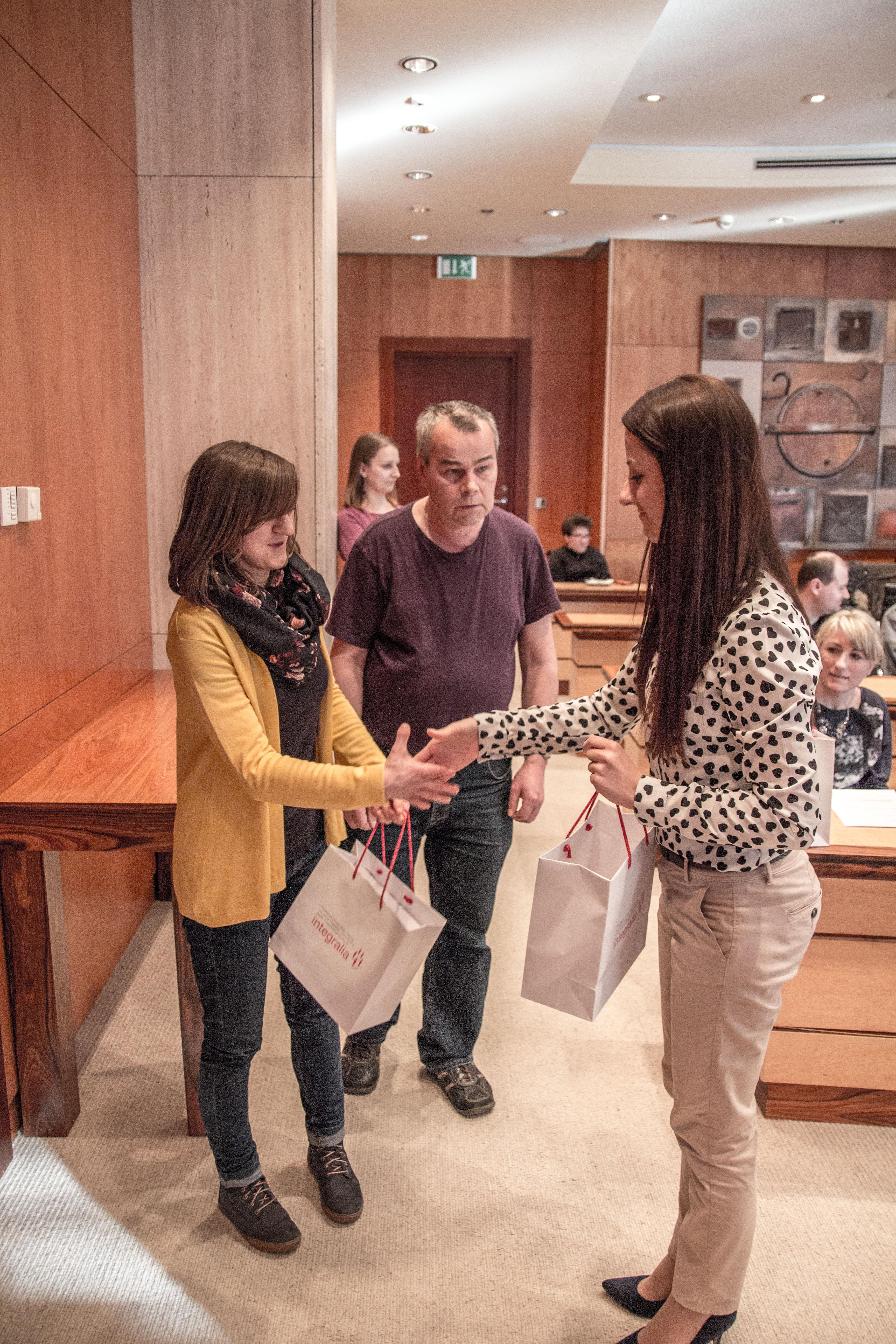 Wręczenie upominków uczestnikom spotkania przez pracownika Fundacji.