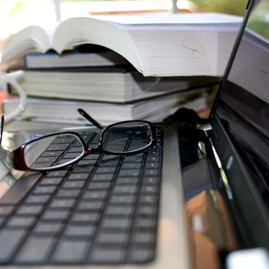 Grafika przedstawia laptopa , gdzie na klawiaturze położone są okulary. W tle widać stos książek