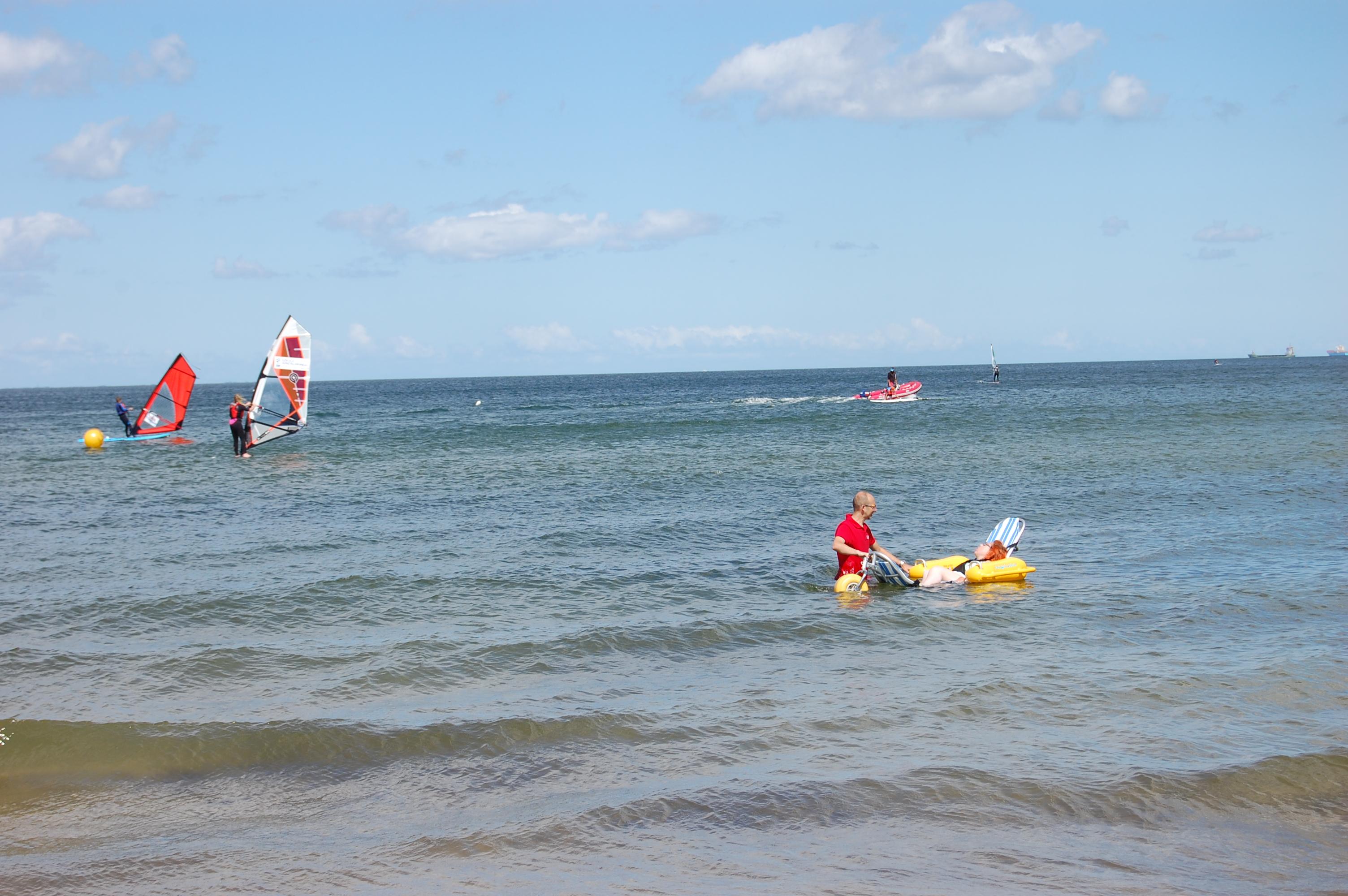 Dziewczyna zanurzona w morzu, siedząca na amfibii. Przy niej stoi opiekun.