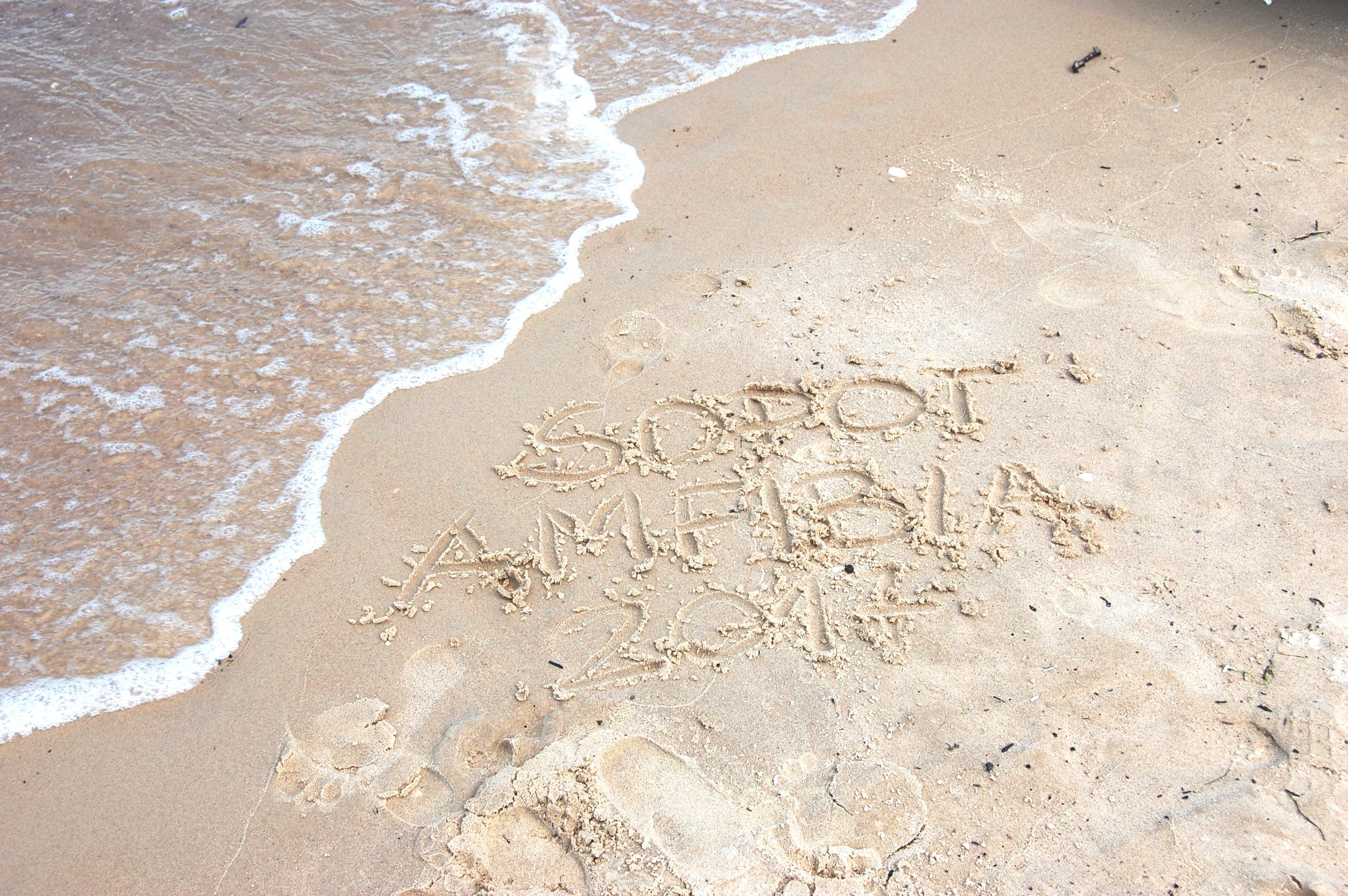 """zdjęcie brzegu, gdzie na piaski jest napis: """"Sopot. Amfibia 2017"""""""