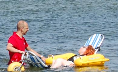 Osoba zanurzona w wodzie, siedząca na amfibii. Stoi przy niej opiekun