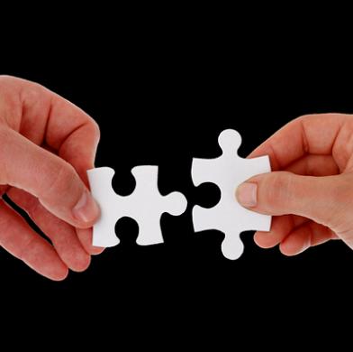 dwie dłonie trzymające dwa pasujące do siebie puzzle