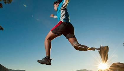 Skaczący mężczyzna na tle panoramy zawierającej góry oraz jezioro