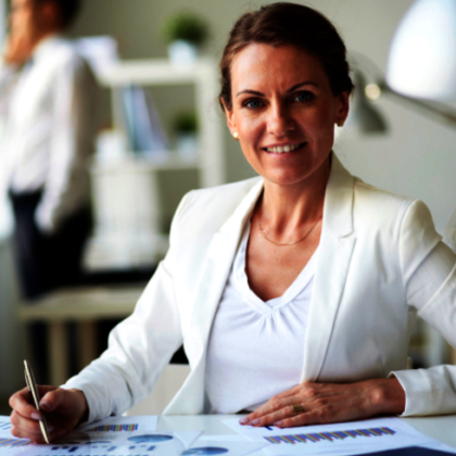 Kobieta siedząca przy biurku-pracownik biurowy.
