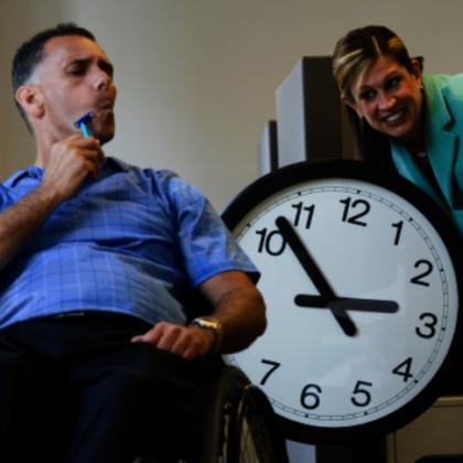 Grafika przedstawia siedzącego na wózku inwalidzkim mężczyznę, który trzyma w ręku maszynke do golenia. na środku widoczny jest duży zegar, a zza niego wygląda uśmiechnięta kobieta.
