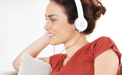 Kobieta w słuchawkach na uszach korzysta z laptopa.