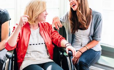 dwie uśmiechnięte koleżanki, jedna z nich siedzi na parapecie, druga na wózku inwalidzkim