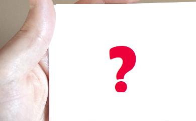 biała kartka ze znakiem zapytania na środku. Widoczna też trzymająca kartkę dłoń.