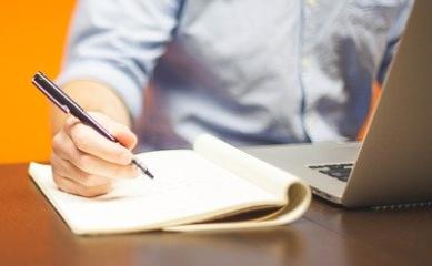 mężczyzna siedzi przy komputerze, robi notatki w notesie.