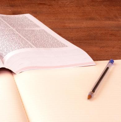 zeszyt i długopis, w tle gruba książka