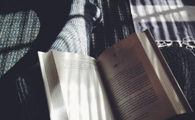 Na zdjęciu widać książkę i nogi osoby siedzącej na kanapie.