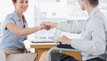 Dwie kobiety witające się przy biurku