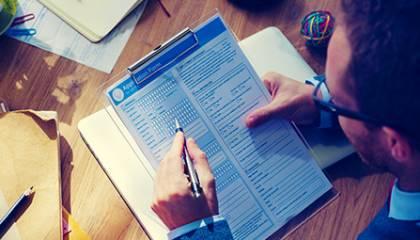 Mężczyzna przy biurku wypełniający formularz